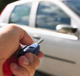 Close-up on a Hand Pointing a Car Key at a Parked Car